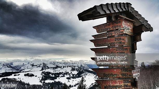sign boards on structure against snow covered landscape - niet westers schrift stockfoto's en -beelden