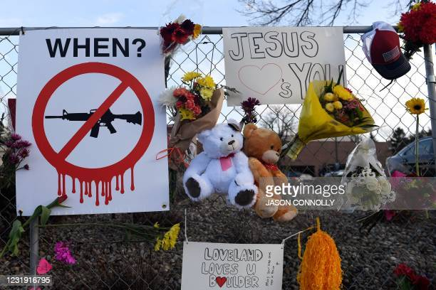 Sign calling for a ban on assault rifles, along with mementos and flowers, hangs from the perimeter fence outside a King Soopers grocery store in...