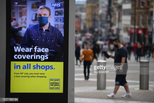A sign calling for the wearing of facemasks in shops is displayed in the city centre of Leeds on July 23 as lockdown restrictions continue to be...
