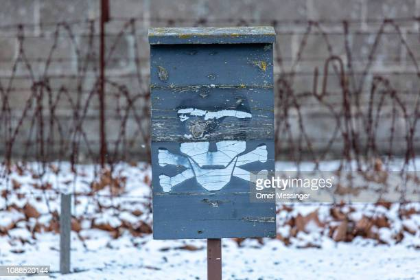 Sign depicting a skull, as a warning from the electric fence surrounding the Sachsenhausen concentration camp memorial on January 25, 2019 in...