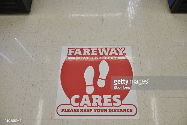 A sign directing customers to distance is displayed on the floor at a Fareway grocery store in Sioux Falls South Dakota US on Wednesday April 15 2020...