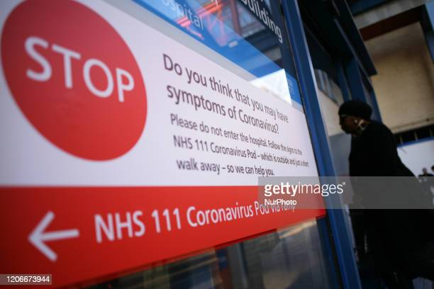 Sign directing people with symptoms of the covid-19 coronavirus to a 'coronavirus pod' isolation unit covers a window of an entrance to St Mary's...