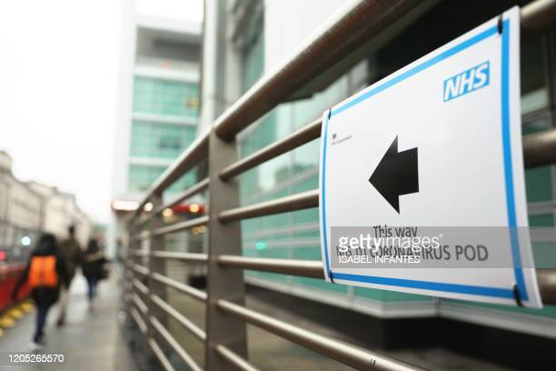 A sign directs directs patients to an NHS 111 Coronavirus Pod testing service area for COVID19 assessment at University College Hospital in London on...
