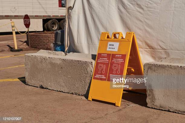 A sign directs employees to a thermal temperature screening tent outside a Smithfield Foods Inc plant in Sioux Falls South Dakota US on Wednesday...
