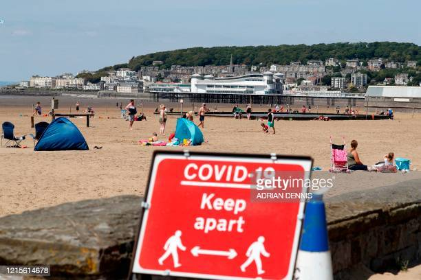 Sign displaying advice on social distancing is displayed at the beach in Weston-super-Mare, south west England on May 27 as lockdown measures are...
