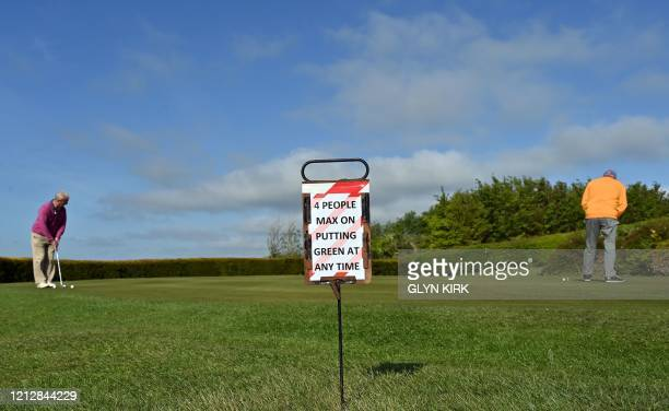 Sign displaying guidelines on the putting green is seen at The Dyke Golf Club on the south coast of England on May 13 as the golf club reopens as...