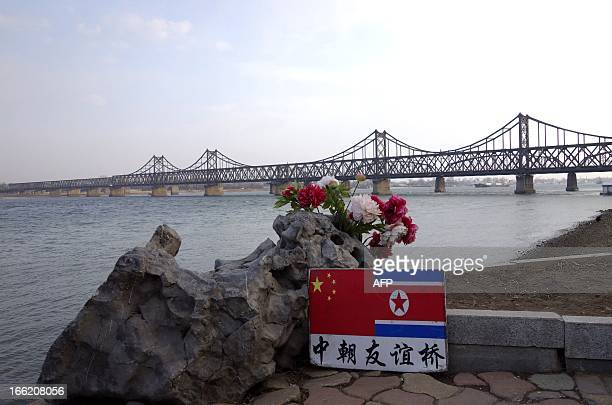 A sign displaying the Chinese and North Korean flags is pictured beside the SinoKorean Friendship Bridge which leads to the North Korean town of...
