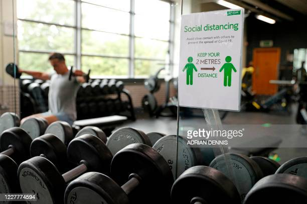 A sign displaying the rules about remaining at a safe distance are attached to a mirror in the gymnasium at Nuffield Health Sunbury Fitness and...
