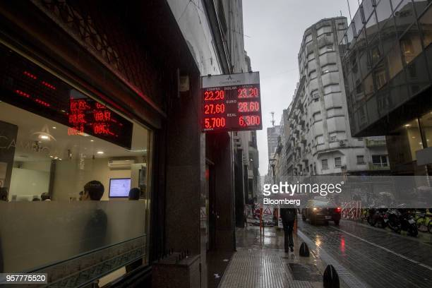 A sign displaying US dollar euro and Brazilian real exchange rates hangs outside of currency exchange house in Buenos Aires Argentina on Thursday May...