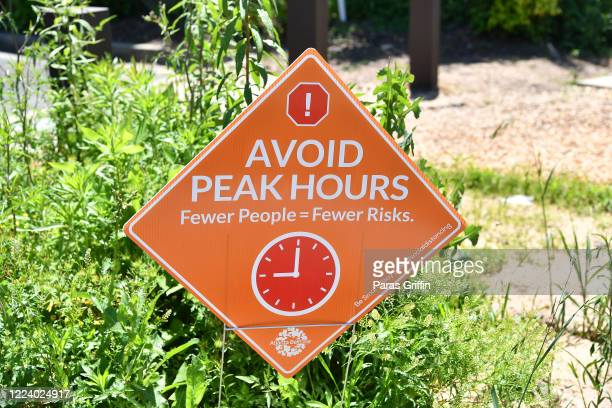 A sign displays Avoid Peak Hours Fewer People = Fewer Risks at the Atlanta Beltline as the coronavirus pandemic continues on May 10 2020 in Atlanta...
