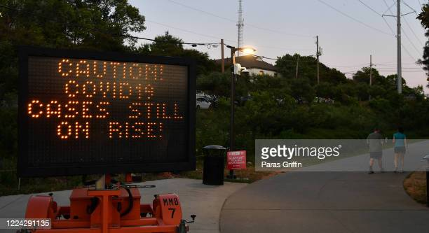 """Sign displays """"Caution! Covid-19 Cases Still On Rise!"""" at the entrance of the Atlanta Beltline near Piedmont Park as the coronavirus pandemic..."""