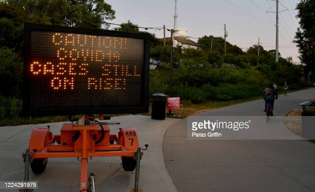 A sign displays Caution Covid19 Cases Still On Rise at the entrance of the Atlanta Beltline near Piedmont Park as the coronavirus pandemic continues...