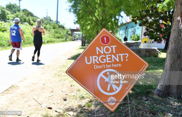 A sign displays Not Urgent Don't be here at the Atlanta Beltline as the coronavirus pandemic continues on May 10 2020 in Atlanta Georgia There are...