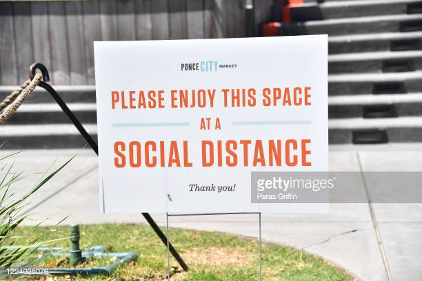 A sign displays Please Enjoy This Space At Social Distance at the Atlanta Beltline as the coronavirus pandemic continues on May 10 2020 in Atlanta...