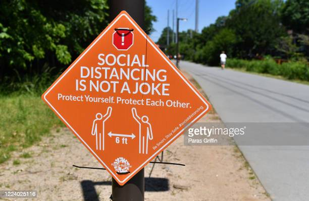 A sign displays Social Distancing Is Not A Joke Protect Yourself Protect Each Other at the Atlanta Beltline as the coronavirus pandemic continues on...