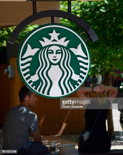 A sign embellished with the Starbucks logo hangs near the entrance to the Starbucks coffee shop in Aspen Colorado The coffeehouse chain is...