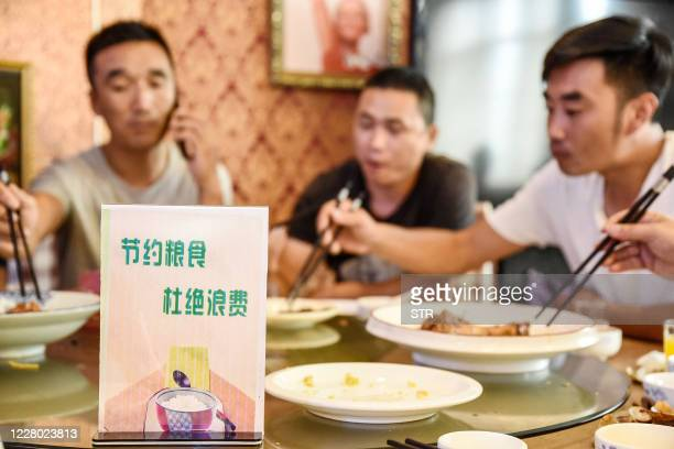 Sign encouraging people not to waste food is seen at a restaurant in Handan in China's northern Hebei province on August 13, 2020. - Chinese diners...