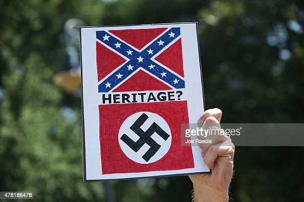 A sign equates the confederate flag with the nazi flag as people attend a protest in support of a confederate flags removal from the South Carolina...