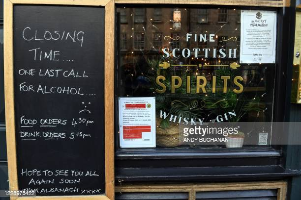 Sign explaining reasons for closing is seen on the door of a bar in Edinburgh on October 9 as new restrictions come into force to combat the spread...
