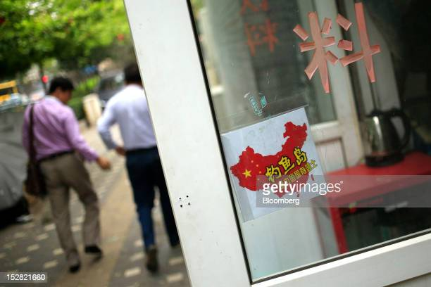 A sign featuring the Chinese flag and the Chinese characters for Diaoyu Islands is displayed on the door of a store in Beijing China on Thursday Sept...