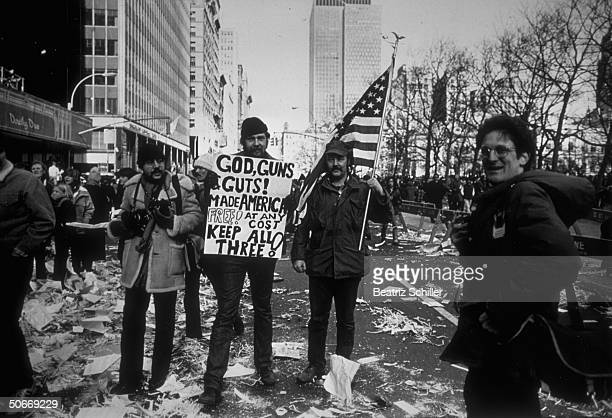 Sign flagcarriers on confettistrewn lower Broadway street during ticker tape parade celebrating release of American hostages after 444 days of...