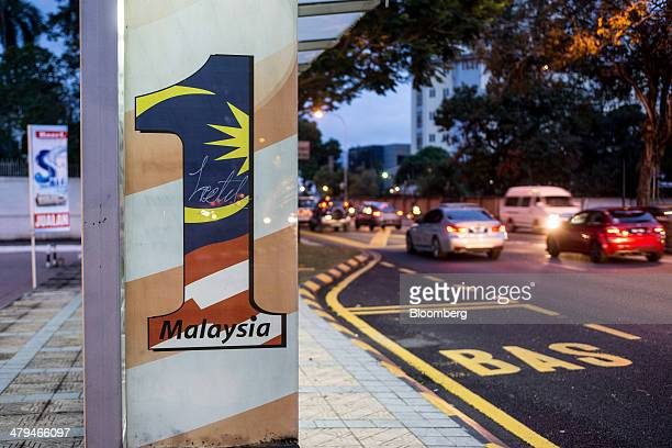Sign for 1Malaysia, a slogan adopted by Malaysian Prime Minister Najib Razak, is displayed at a bus stop in Kuala Lumpur, Malaysia, on Tuesday, March...