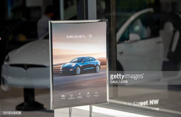 A sign for a Tesla Model 3 sedan is seen at a Tesla showroom in Washington DC on August 8 2018 Tesla's board of directors said Wednesday it will...