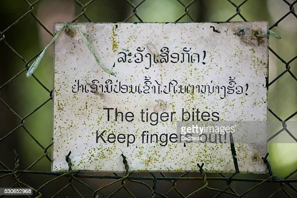 A sign for a tiger biting on a fence in Laos, Thailand