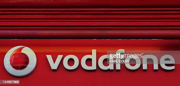 Sign for a Vodafone store is pictured in central London on May 22, 2012. British mobile phone giant Vodafone on Tuesday said annual net profits...