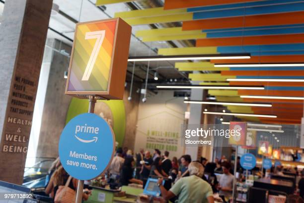 A sign for Amazoncom Inc Prime members hangs on display at the checkout counter during the grand opening of a Whole Foods Market Inc location in...