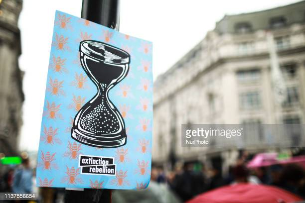 A sign for climate change activist group Extinction Rebellion stands fixed to a traffic light pole at Oxford Circus London England on April 16 2019...