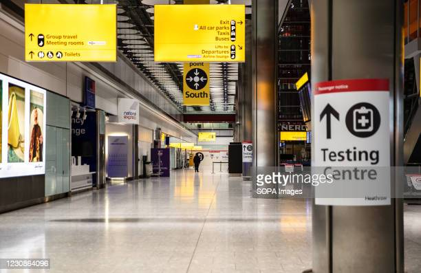 Sign for COVID-19 testing centre is seen at the Heathrow international arrival hall.
