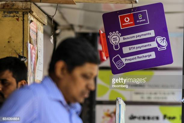 A sign for digital payment service mpesa operated by Vodafone India Ltd hangs at a shop in Bengaluru India on Saturday Feb 4 2017 A relative laggard...