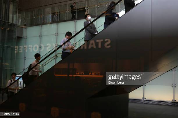 A sign for Starbucks Corp is reflected as morning commuters ascent on an escalator in Tokyo Japan on Monday May 14 2018 Japan is scheduled to release...
