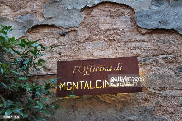 A sign for the clothing store L'officina Di Montalcino 564 is lit in the evening on July 23 2015 in the hilltop town of Montalcino in the region of...