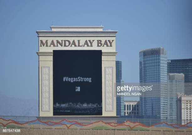 A sign for the Mandalay Bay Hotel showing a message is seen as the motorcade of US President Donald Trump passes by in Las Vegas on October 4 2017...