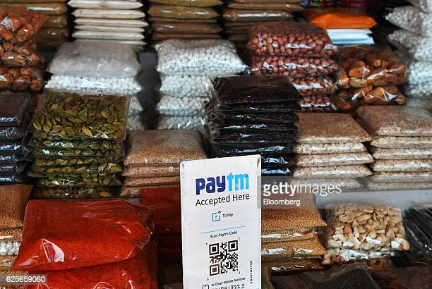 A sign for the PayTM online payment method operated by One97 Communications Ltd is displayed next to bags of spices at a wholesale market in Delhi...
