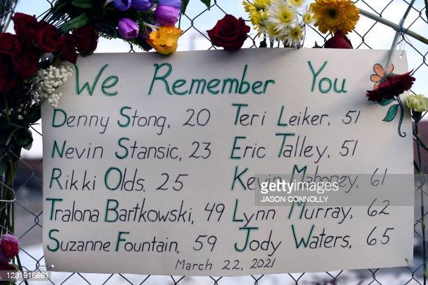 Sign framed with flowers, listing the victims' names, hangs from the perimeter fence outside a King Soopers grocery store in Boulder, Colorado on...