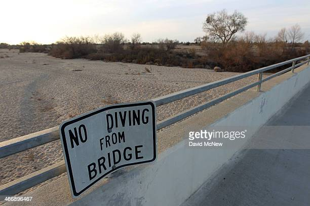 Sign from wetter times warns people not to dive from a bridge over the Kern River, which has been dried up by water diversion projects and little...