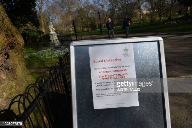 A sign giving social distancing guidlines is seen at an entrance to St James's Park in central London in the morning on March 24 2020 after Britain...