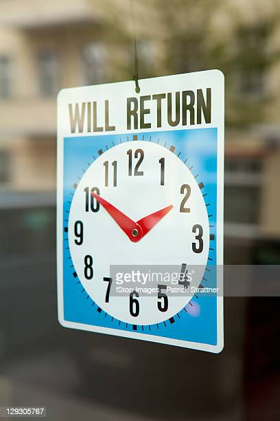A WILL RETURN sign hanging in the window of a shop door
