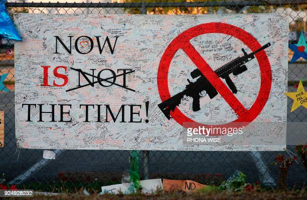 A sign hangs on a fence one at Marjory Stoneman Douglas High School in Parkland Florida on February 27 2018 Florida's Marjory Stoneman Douglas high...