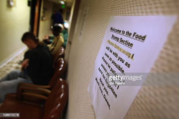 A sign hangs on a wall as people wait in line to appy for the federal food stamps program on February 10 2011 in Fort Lauderdale Florida Recent...