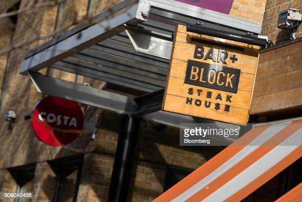 A sign hangs outside the entrance to a Bar and Block restaurant operated by Whitbread Plc in London UK on Wednesday Jan 17 2018 The hotel and...