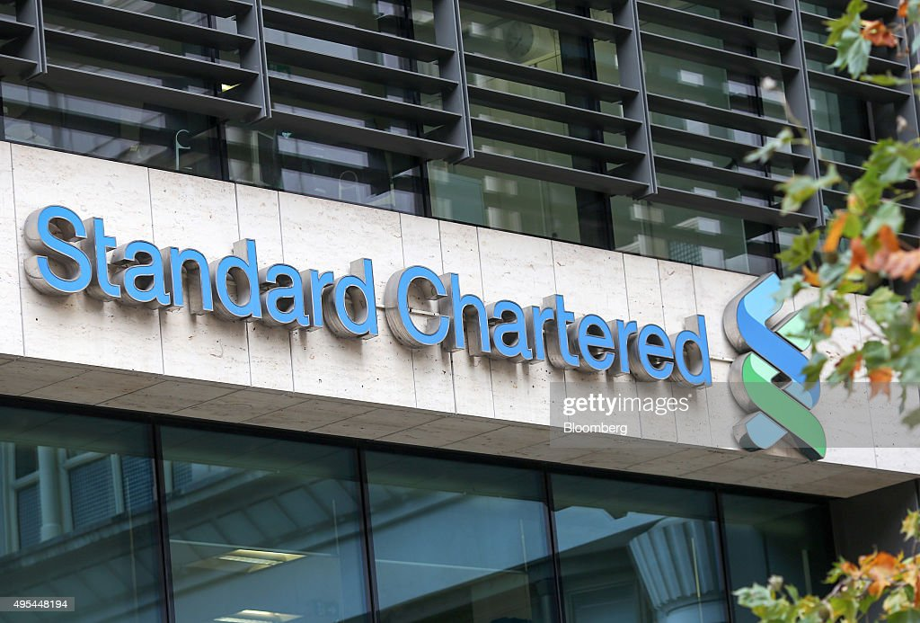 A sign hangs outside the headquarters of Standard Chartered Plc in London, U.K. on Tuesday, Nov. 3, 2015. Standard Chartered Plc dropped the most in more than three years after the lender said it plans to eliminate 17 percent of its workforce, scrap the dividend and tap investors for $5.1 billion as Chief Executive Officer Bill Winters seeks to restore profit growth. Photographer: Chris Ratcliffe/Bloomberg via Getty Images