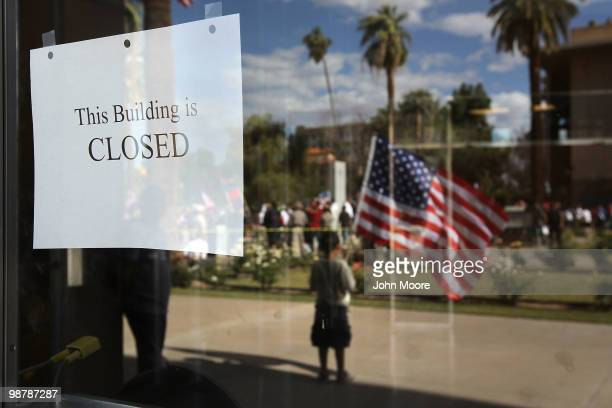 A sign hangs taped to the window of the Arizona state senate building as demonstrators protest Arizona's new immigration enforcement law during a May...