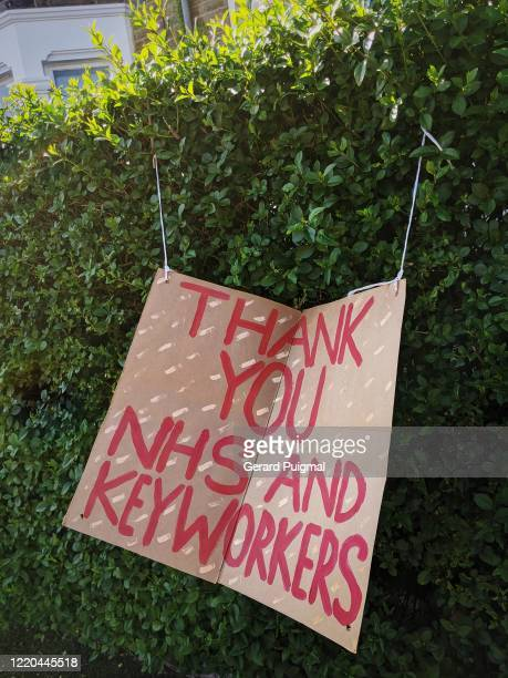 sign hung on a bush in front of a house to support nhs staff and keyworkers - essential workers stock pictures, royalty-free photos & images