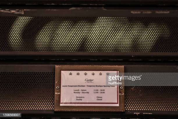 Sign in a high fashion store indicates reduced working hours due to the Coronavirus emergency, on March 11 in Rome, Italy. The Italian government has...