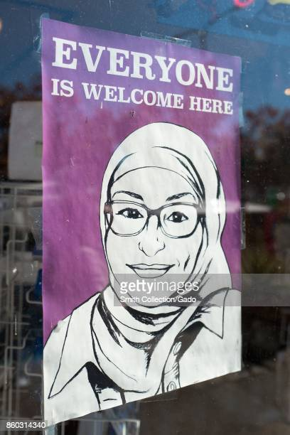 Sign in a store window in the Gourmet Ghetto neighborhood of Berkeley California reading Everyone is Welcome Here and featuring an image of a smiling...