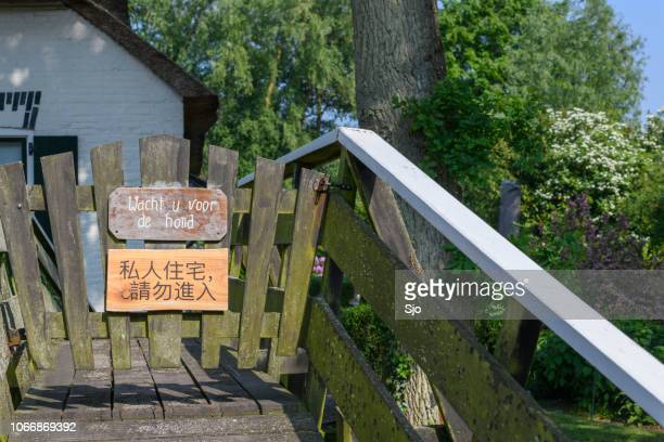 Sign in Dutch and Chinese to wait for to dog to keep tourists away in Giethoorn in The Netherlands